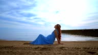 Woman lying on sea beach in blue dress. Pregnant woman relaxing on beach video