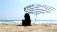 Woman lying on the beach sunbathing under parasol video