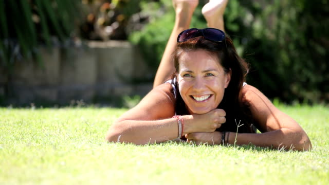 Woman lying on the lawn smiling to camera video