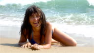 Woman lying on the sand, the sea waves splashing in her body video