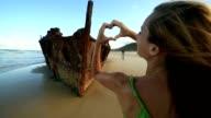 Woman makes heart shape finger frame on Fraser Island video
