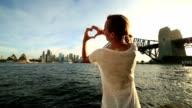 Woman makes heart shape finger frame on Sydney skyline video