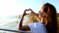 Woman makes heart shape finger frame to Twelves Apostles-Australia video