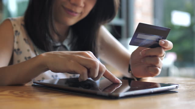 Woman making an online credit card purchase on Tablet PC video