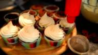 Woman making creamy top of cupcakes closeup video