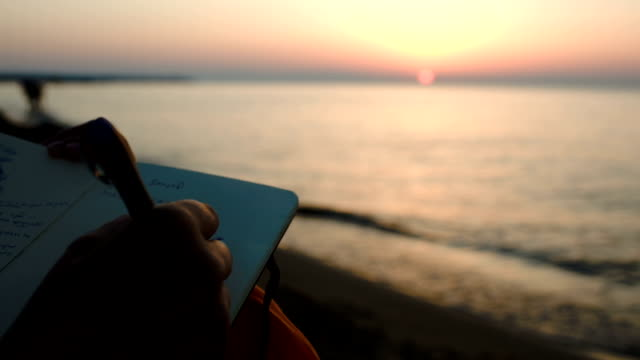Woman making notes sitting by sea at sunset video