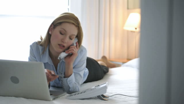 Woman Making Phone Booking In Hotel Room; HD Photo JPEG video