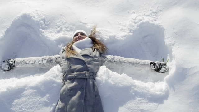 SLOW MOTION CLOSE UP: Woman making snow angels in powder video