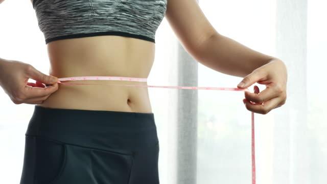 Woman measuring waist video