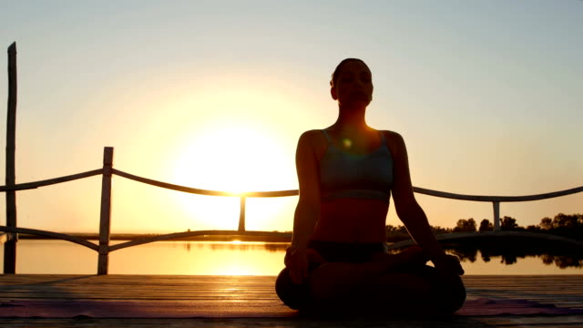 Woman meditating at beach on sunset video