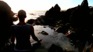 Woman meditating at sunset video
