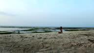 Woman meditating at sunset video