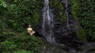 Woman meditating beside waterfall. Tropical rainforest. Holiday relaxation video