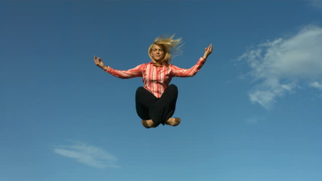 Woman meditating in mid air, slow motion video