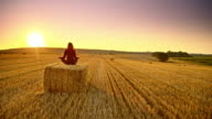 DS Woman meditating on a bale of wheat at sunset video