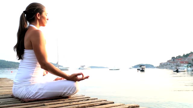 Woman meditating on a wooden pier video