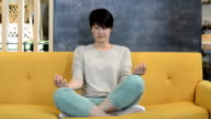 Woman Meditating on Yellow Couch video