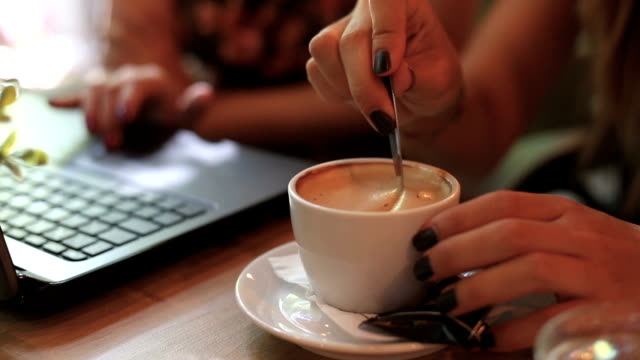 Woman mixing cafe in coffee shop with her friend video
