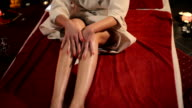 Woman moisturizes the skin on the legs. video