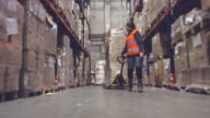 Woman moving boxes in a warehouse video