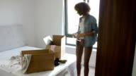Woman Moving Into New Home Unpacking Clothes In Bedroom video