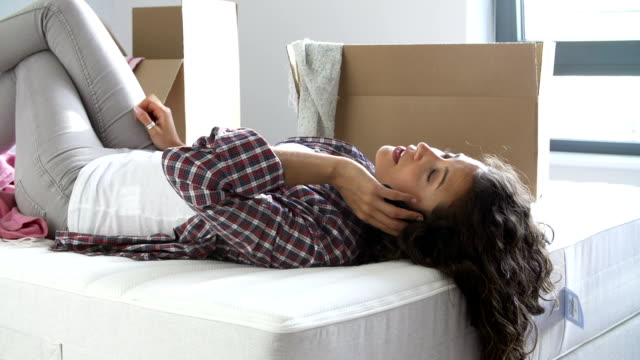 Woman Moving Into New Home Using Mobile Phone Lying On Bed video