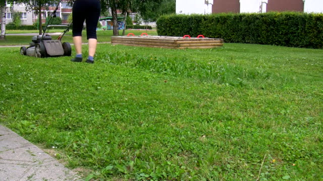 Woman mowing the lawn video