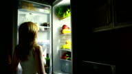 Woman night takes an apple from the fridge. hungry woman video