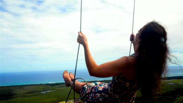 woman on a swing and a blue sky with ocean and mountain video