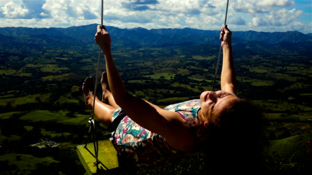Woman on a swing and blue azur sky with mountain video