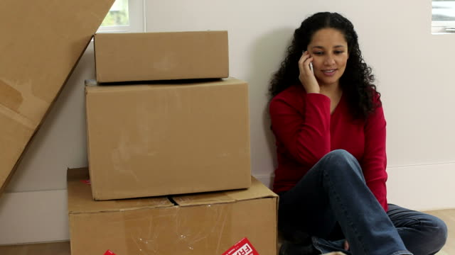 Woman on cell phone with unpacked boxes video