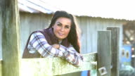 Woman on farm outside barn, walks up to wooden fence video