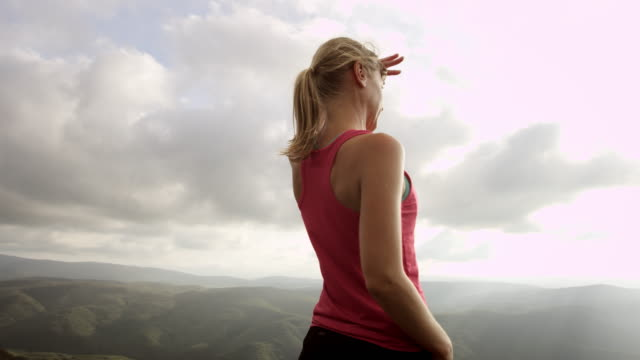 PAN Woman on mountain top looking into the distance video