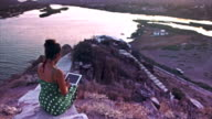Woman on promontory using tablet video