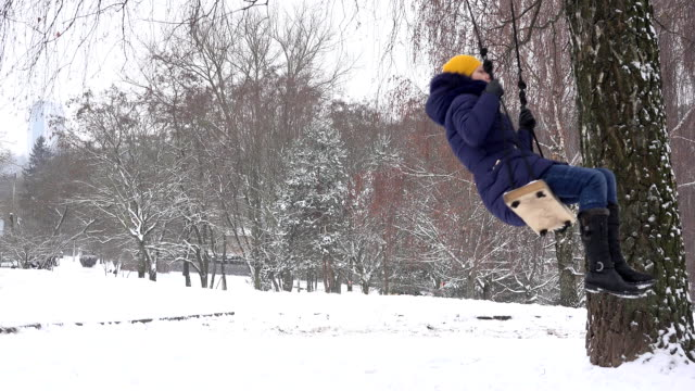 Woman on rope and wood swing under birch tree during winter time. FullHD video