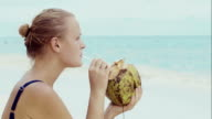 Woman on the beach drinking from coconut video