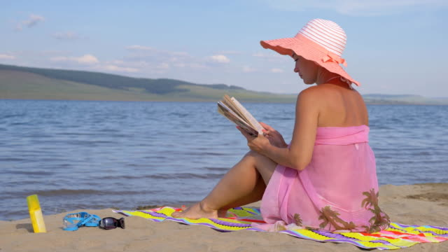 Woman on the beach reading a book. video