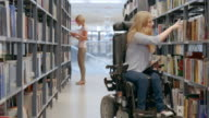 DS Woman on wheelchair finding right book on library shelf video