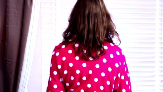 Woman opening blinds, looking through window. morning. video