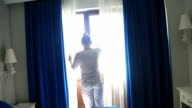 Woman opening blue curtains video