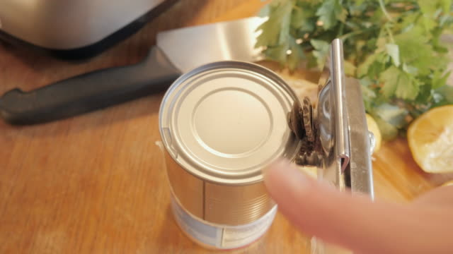 Woman Opens a Tin Can with a Can Opener video