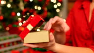 Woman opens Christmas gift, closeup video