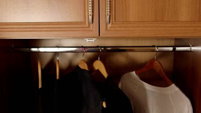 Woman opens doors of half empty wardrobe video