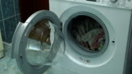 Woman opens the lid of the washing machine. She takes a clean wet laundry from the washing machine. Woman closes the lid of the washing machine. video