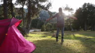 Woman outstretches arms at sunrise next to tent video