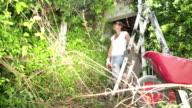 Woman Overwhelmed by Overgrown Garden video