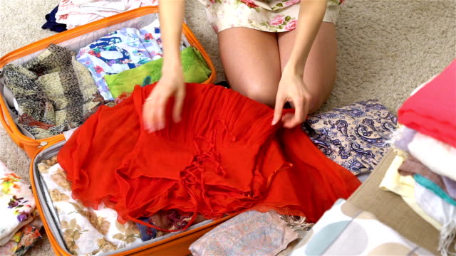 woman packing a luggage for a new journey, red dress, slow motion video