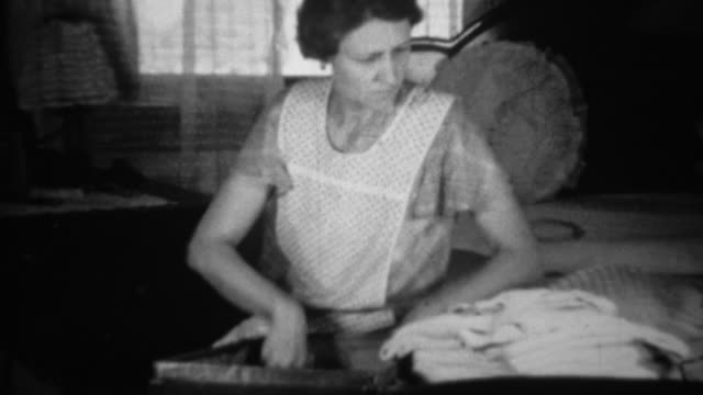 1936: Woman packing clothes into suitcase seated in living room. video