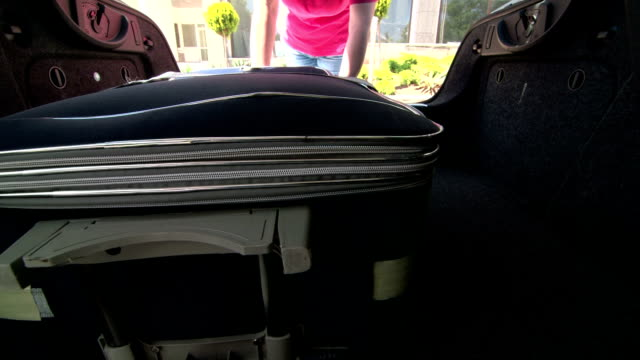 Woman packing her luggage into car trunk inside view video