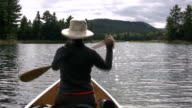 Woman paddles canoe. Sunny water. POV from stern. video